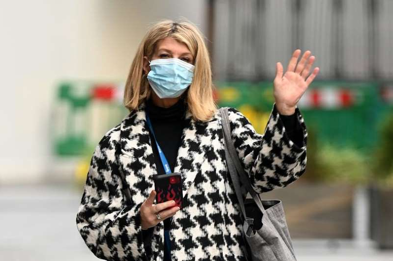 a person wearing sunglasses posing for the camera: Kate Garraway wore a black and white coat as she left the radio station