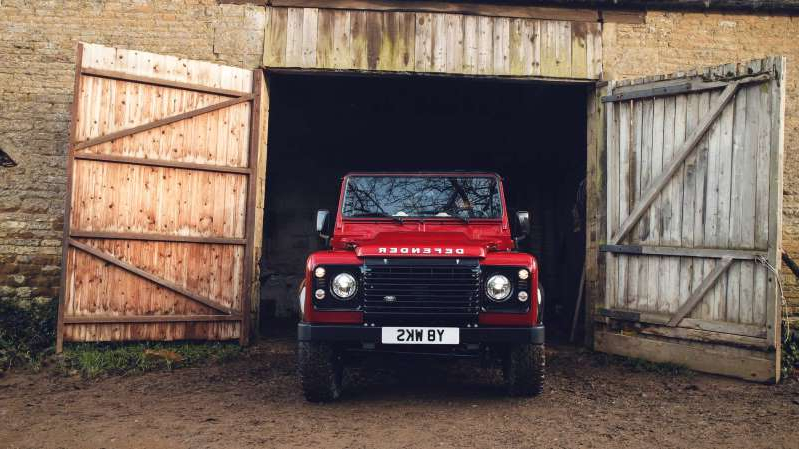 a truck is parked in front of a fence: Land Rover Defender Works V8