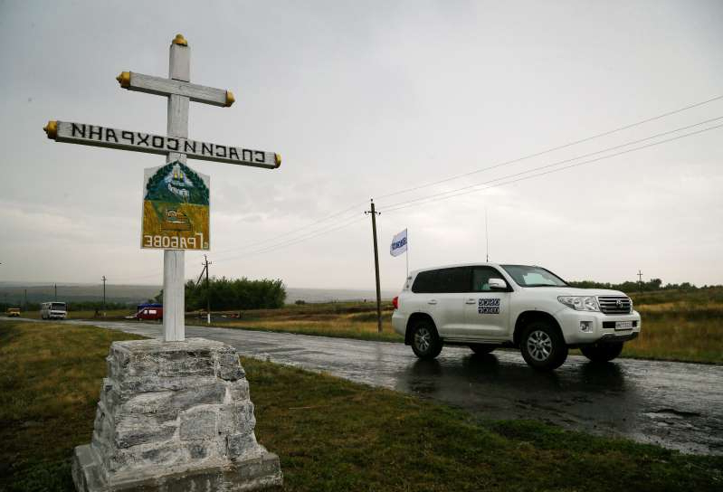 a truck that has a sign on the side of a road: FILE PHOTO: An OSCE car drives past the crash site of Malaysia Airlines Flight MH17 plane on the anniversary of the incident, outside the village of Hrabove in eastern Ukraine