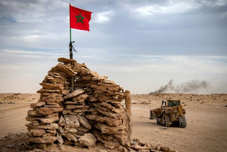a truck that is sitting on a rock: A bulldozer passes by a hilltop manned by Moroccan soldiers on a road between Morocco and Mauritania in Guerguerat located in the Western Sahara, on November 23