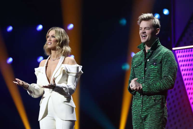 Joel Creasey, Delta Goodrem standing on a stage: Hosts Joel Creasey and Delta Goodrem speak during the 2020 ARIA Awards at The Star on November 25, 2020 in Sydney, Australia.