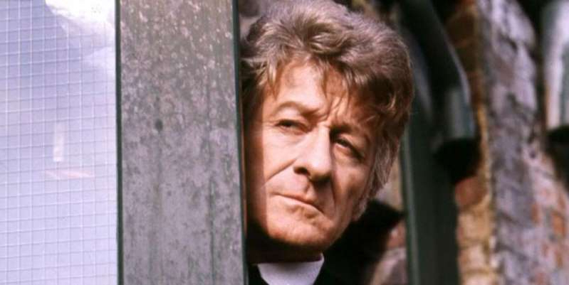 Jon Pertwee standing in front of a brick wall: Doctor Who announces classic series will get special edition boxset as season 8, starring Jon Pertwee and Katy Manning, becomes available for pre-order.