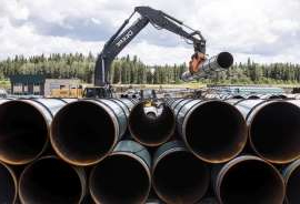 a close up of a traffic light: Pipe for the Trans Mountain pipeline is unloaded in Edson, Alta. on Tuesday June 18, 2019.