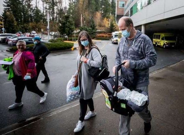 a couple of people that are standing in the road: Dave McIntosh leaves the Abbotsford Regional Hospital with his newborn baby and assistance from his sister in Abbotsford, B.C., on Wednesday, Nov. 25, 2020.