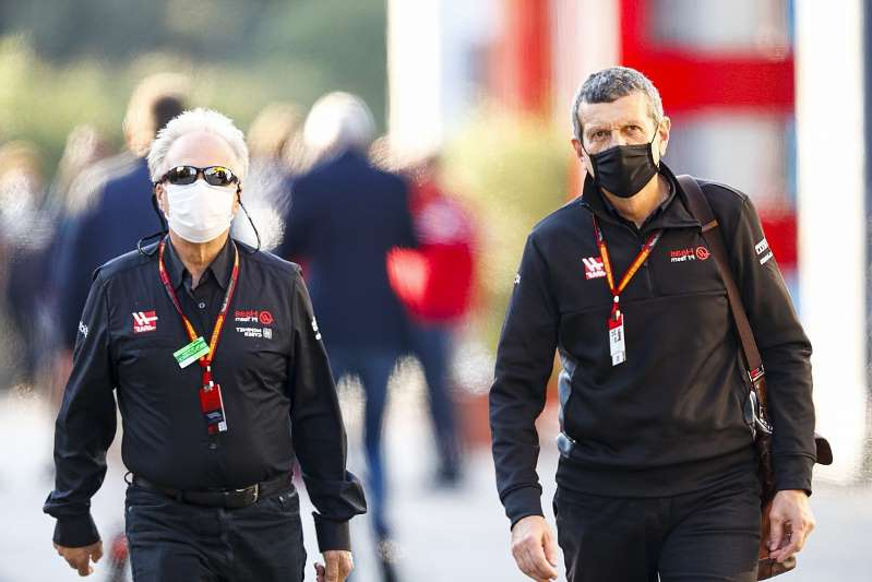 a couple of people that are talking to each other: Steiner: Haas survival biggest achievement of 2020