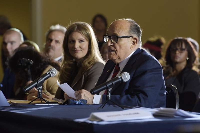 a group of people sitting at a table: Rudy Giuliani, personal lawyer to President Trump, speaks at a news conference Wednesday in Gettysburg, Pa.
