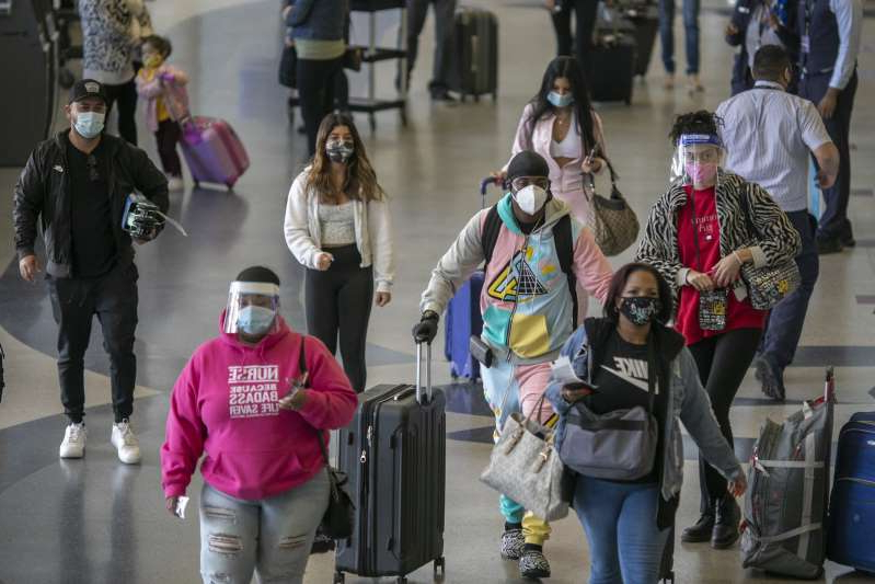 a group of people wearing costumes: Holiday travelers pass through Los Angeles international Airport on Thanksgiving eve as the COVID-19 spike worsens and stay-at-home restrictions are increased on November 25, 2020, in West Hollywood, California. According to the TSA's records, more people traveled on Wednesday than on any other day since March 16.