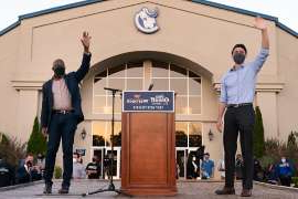 a man standing in front of a building: Democratic U.S. Senate candidates Raphael Warnock and Jon Ossoff are seen at a campaign event on November 19, 2020 in Jonesboro, Georgia. A group of romance novelists have raised nearly 0,000 for Warnock and Ossoff in their upcoming runoff races.