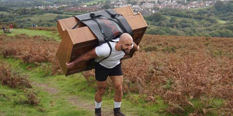 a man that is standing in the grass: The Welsh fitness fanatic hauled 400lb uphill for charity