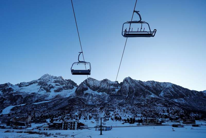 a person flying through the air on a snow covered mountain: A closed chairlift is seen Thursday at the ski resort of Passo Tonale in Passo del Tonale, Italy.