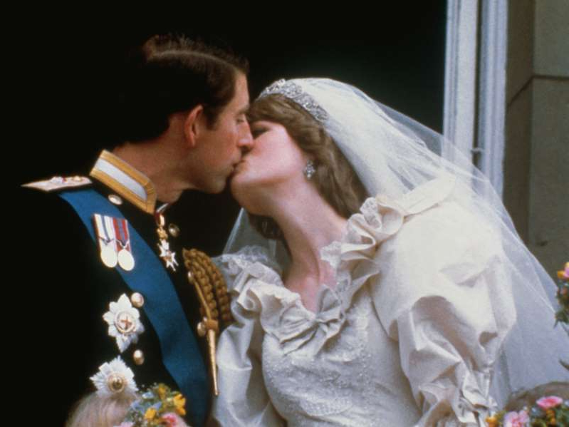 a person holding a baby: Princess Diana and Prince Charles kiss on the balcony of Buckingham Palace, after their wedding ceremony.