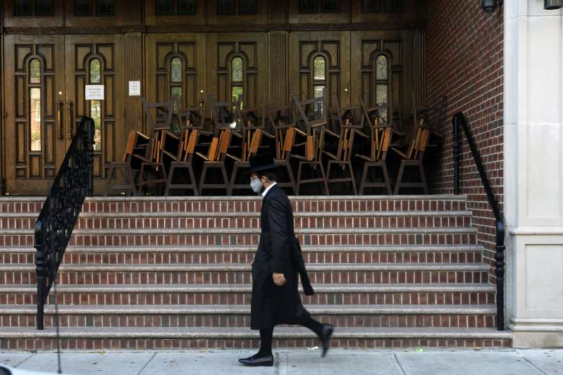 a person standing in front of a building: Residents walk by a synagogue in the Brooklyn neighborhood of Borough Park on October 07, 2020 in New York City.