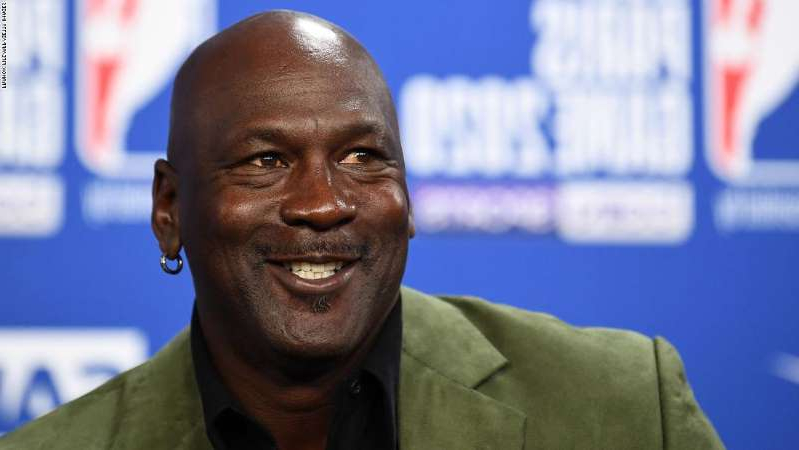 Michael Jordan wearing a suit and tie: Former NBA star and owner of Charlotte Hornets team Michael Jordan looks on as he addresses a press conference ahead of the NBA basketball match between Milwaukee Bucks and Charlotte Hornets at The AccorHotels Arena in Paris on January 24, 2020. (Photo by FRANCK FIFE / AFP) (Photo by FRANCK FIFE/AFP via Getty Images)