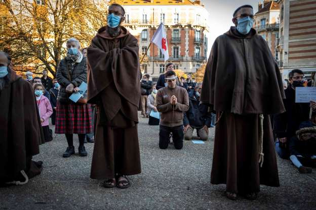 Slide 1 of 62: Monks and Catholic faithful take part in a rally to protest COVID-19 restrictions under which masses are banned in churches, on Nov. 22, 2020, outside the Saint-Etienne cathedral in Toulouse, southern France, during a second national lockdown in France aimed at curbing the spread of the COVID-19 pandemic, caused by the novel coronavirus.