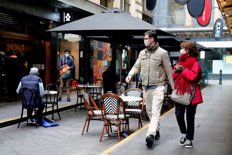 a group of people standing in front of a building: People walk past a cafe after the coronavirus disease (COVID-19) restrictions were eased for the state of Victoria, in Melbourne