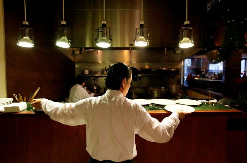 a man standing in a kitchen: A waiter reaches for plates at a restaurant in San Francisco in a Dec.7, 2011 file photo. THE CANADIAN PRESS/AP/Eric Risberg, File
