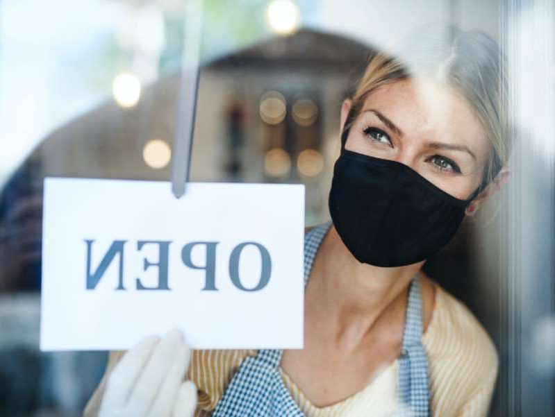 a person wearing a hat: Coffee shop woman owner with face mask, open after lockdown quarantine.
