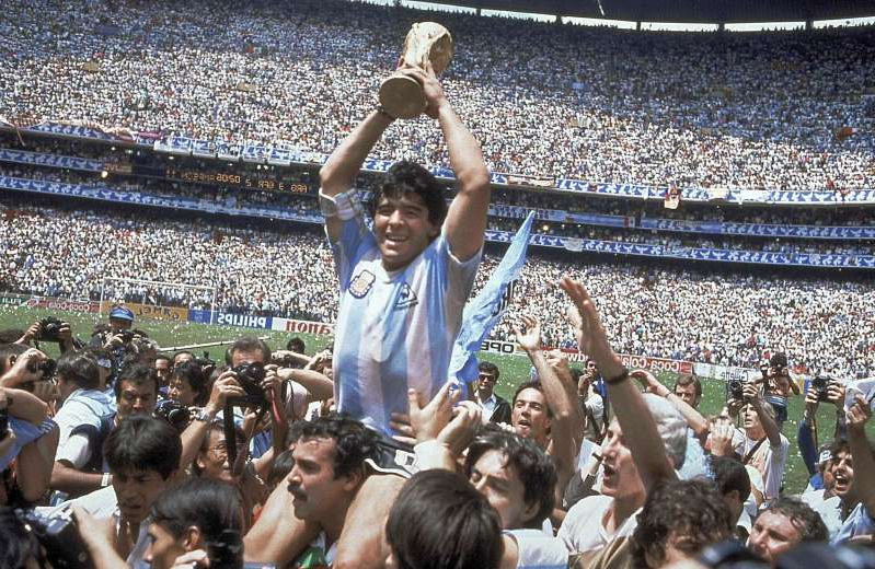 Diego Maradona et al. jumping in front of a crowd: Image: Diego Maradona holds up the 1986 World Cup trophy (Carlo Fumagalli / AP)