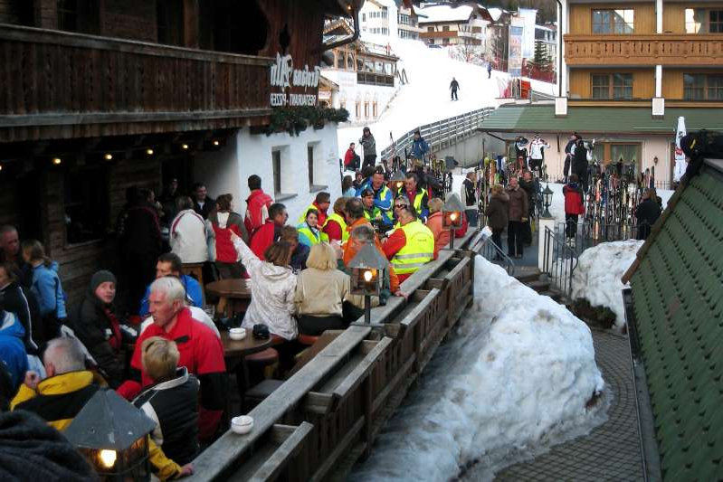 a crowd of people walking in the snow: AUSTRIA - APRIL 04: Skiers are able to ski right into this bar and restaurant at the Ischgl ski resort in Ischgl, Austria, as seen on Feb. 22, 2008. Ischgl is located in the Paznaun Valley, a 30-kilometer-long (19-mile) area that includes three smaller resorts, and counting the adjacent Samnaun ski resort in Switzerland, there are 67 lifts in the region. (Photo by Peter J. Brennan/Bloomberg via Getty Images)