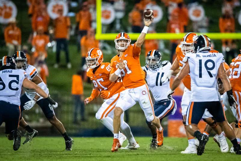 a group of football players on a field: Clemson quarterback Trevor Lawrence throws a pass during this team's game against Virginia at Memorial Stadium.