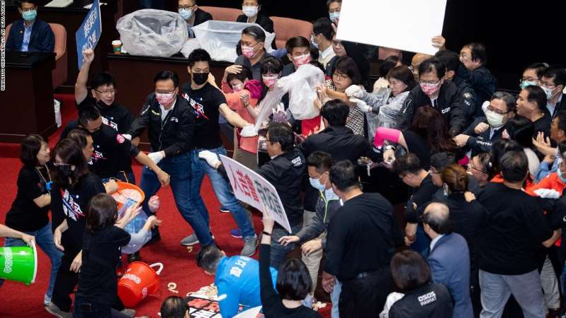 a group of people standing in front of a crowd: Kuomintang (KMT) lawmakers throw pig offal on the podium in Taiwan's parliament in Taipei, on November 27, 2020.