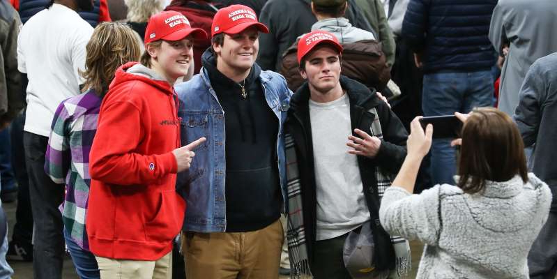 a group of people standing in front of a crowd: Young supporters of President Donald Trump pose for a photographs at a campaign rally in Toledo, Ohio, on January 9, 2020. Scott W. Grau/Icon Sportswire via Getty Images