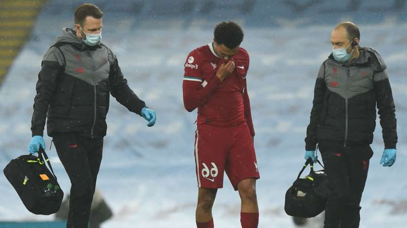 a group of people that are standing in the snow: Liverpool defender Trent Alexander-Arnold heads off against Manchester City.