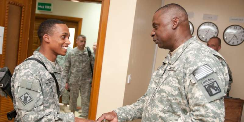 a man standing in a room: US Army Gen. Lloyd J. Austin III, commander of United States Forces - Iraq, presents a coin for an enlisted soldier at Operating Base Adder, Iraq. Defense Department