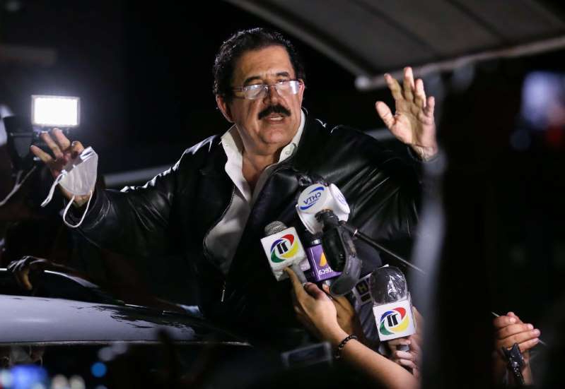 a man standing on a stage: Manuel Zelaya, former President of Honduras, speaks to the media after been held and later released by authorities at Toncontin International Airport on November 27, 2020 in Tegucigalpa, Honduras. Zelaya said he was detained after $18,000 was found in his luggage.