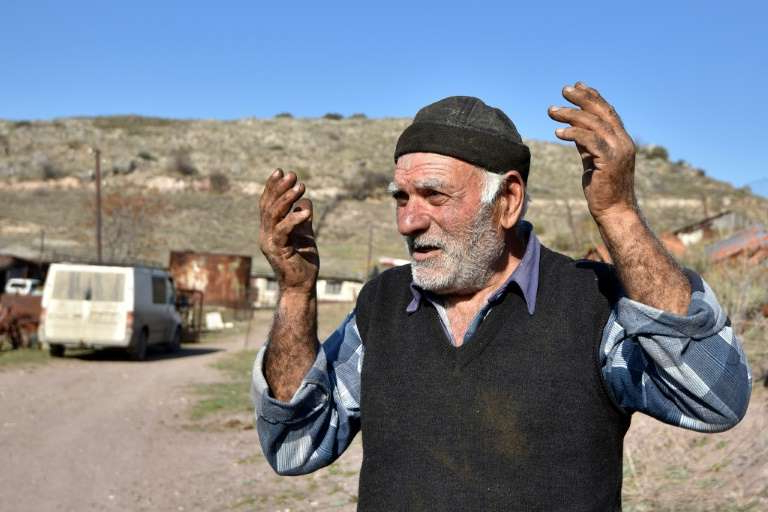 a man standing on top of a dirt road: Pomegranate grower Zhorik Grigoryan, 73, nearly lost his pomegranate field in the fighting