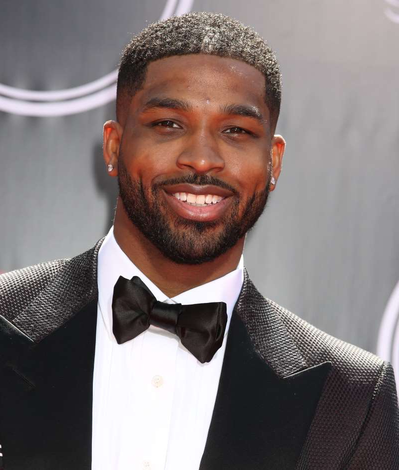 Tristan Thompson wearing a suit and tie smiling at the camera