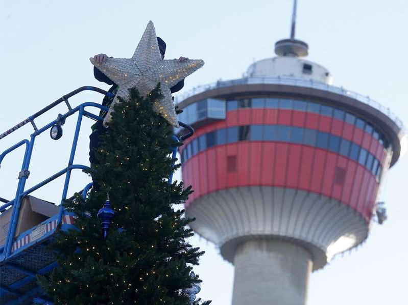 a close up of a tower: A city employee decorates the Christmas tree at Olympic Plaza in Calgary on Wednesday, Nov. 25, 2020.