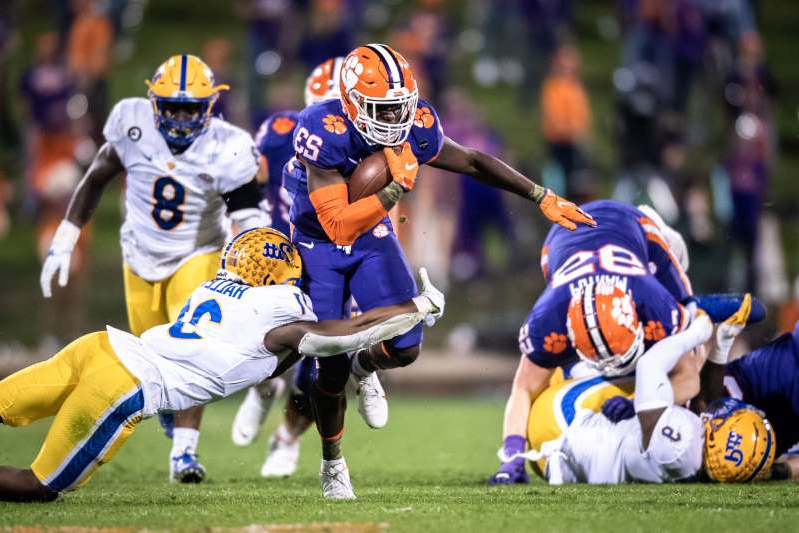 a group of baseball players playing a football game: Clemson running back Lyn-J Dixon (23) is tackled by Pittsburgh defensive back Erick Hallett during the third quarter at Memorial Stadium.