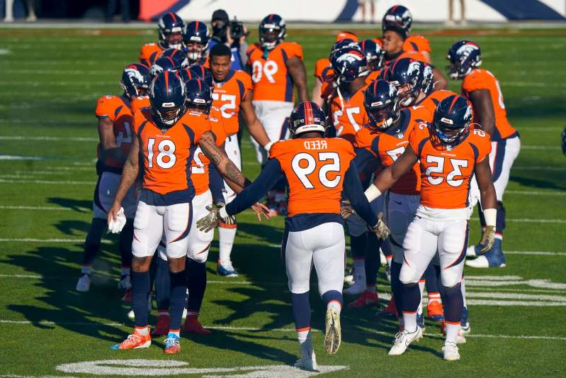 a group of football players on a field: Denver Broncos linebacker Malik Reed (59) is greeted by teammates during player introductions before the start of an NFL football game against the Miami Dolphins Sunday, Nov. 22, 2020, in Denver.