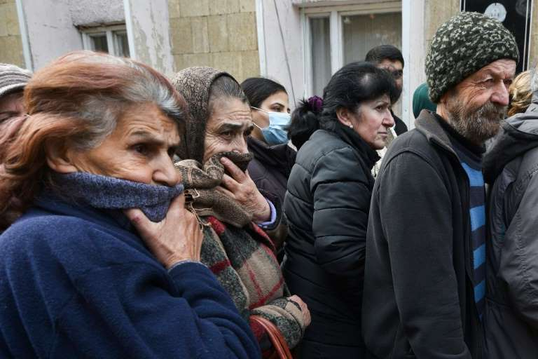 a group of people that are talking to each other: People queue for a food package in Karabakh's main city Stepanakert