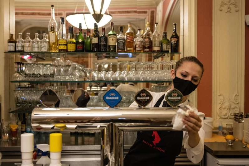 a person holding a glass of wine: A worker cleans a beer tap at Cafe Louvre ahead of the introduction of new coronavirus restrictions in Prague, Czech Republic, on Tuesday, Oct. 13, 2020. The Czech Republic tightened social distancing rules and closed down schools, restaurants and bars through early November as it seeks to stem the European Union's fastest surge in the coronavirus pandemic.