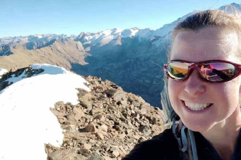 a person wearing sunglasses standing in front of a mountain: Esther Dingley sent this photo of her atop a mountain on Sunday