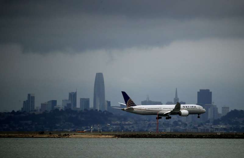 a plane flying over a body of water: File photo: A United Airlines plane lands at San Francisco International Airport on March 06, 2020. The airline's planes are being used to fly potential COVID-19 vaccine shots into and around the United States.