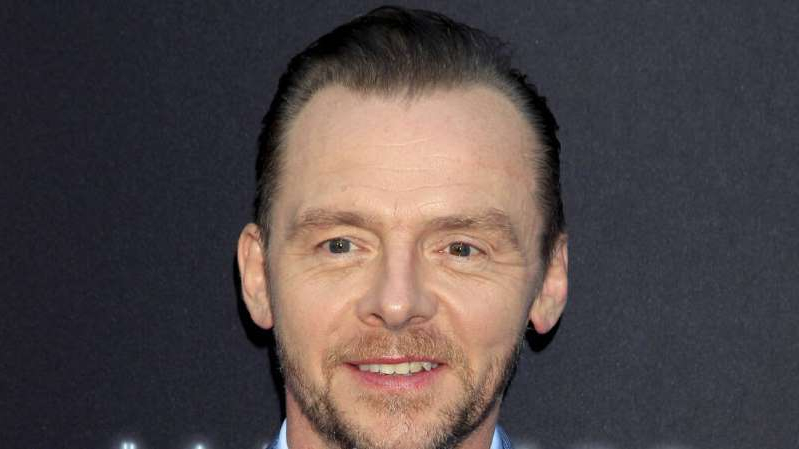 Simon Pegg wearing a suit and tie smiling and looking at the camera