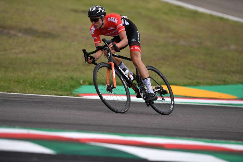 a man riding on the back of a bicycle: Tobias Bayer representing Austria in the elite men's road race at the 2020 World Championships in Imola, Italy
