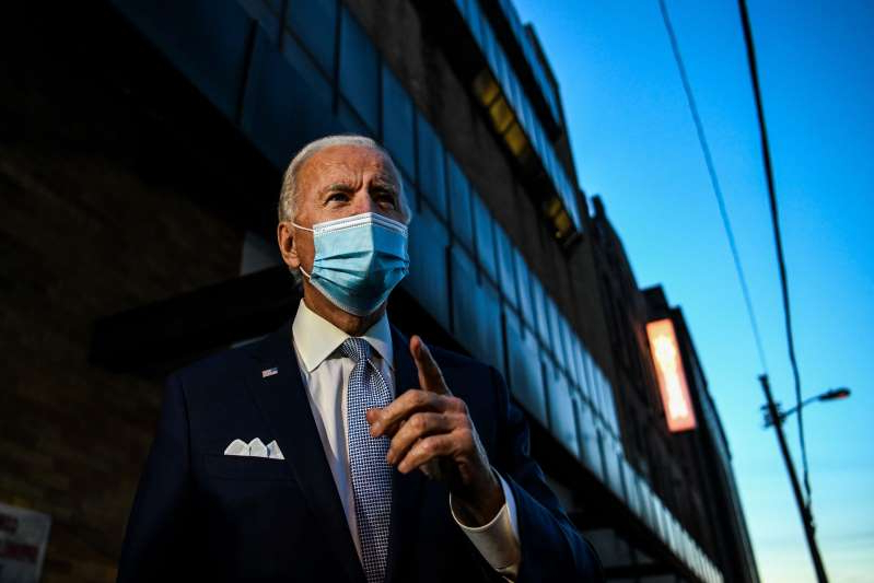 a man wearing a suit and tie talking on a cell phone: Joe Biden talks to the media outside the Queen theatre in Wilmington, Delaware, on November 24, 2020. His favorability ratings have risen, with his standing among Republicans even boosting, according to new polling.