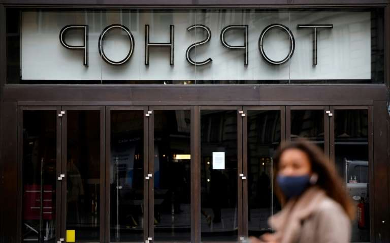 a person standing in front of a store: Arcadia, the owner of a chain of retail clothing stores including Topshop, is struggling to avoid bankruptcy