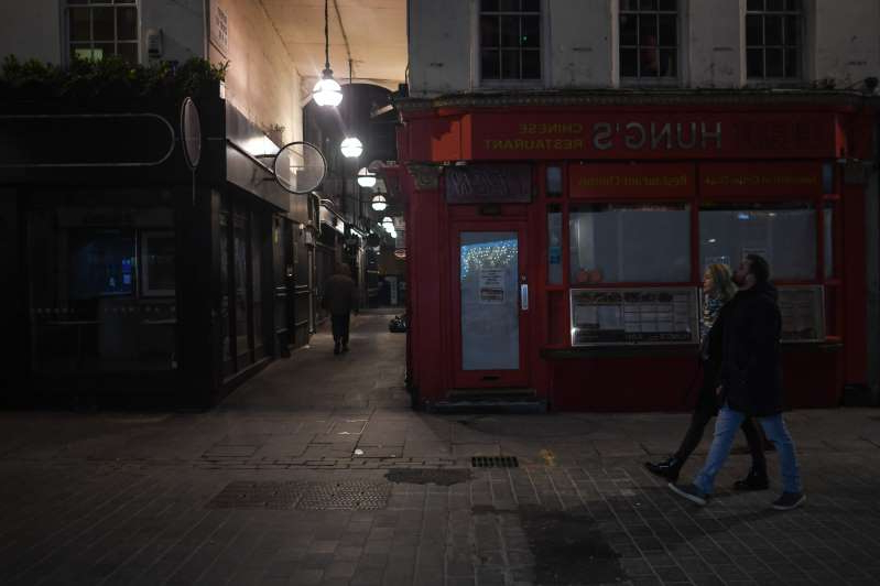 a person walking down a street next to a building: London's Deserted Nightspots Due To Coronavirus Lockdown LONDON, ENGLAND - NOVEMBER 21: General view of Chung's restaurant, which has permanently shut, on November 21, 2020 in London, England. Many of London's bars, clubs and restaurants are facing an uncertain future due to the extended coronavirus lockdown. A tequila bar in Nottingham registered to become a church in an effort to bypass the U.K.'s restrictions.