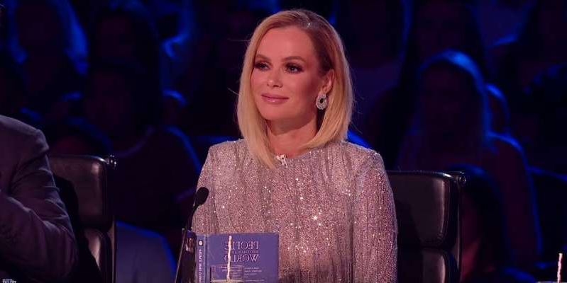 Amanda Holden sitting on a stage: Britain's Got Talent judge Amanda Holden braved the cold and showed off her incredible figure at the same time