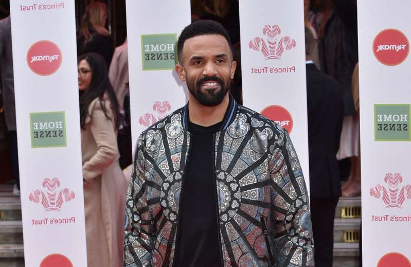 Craig David holding a sign posing for the camera