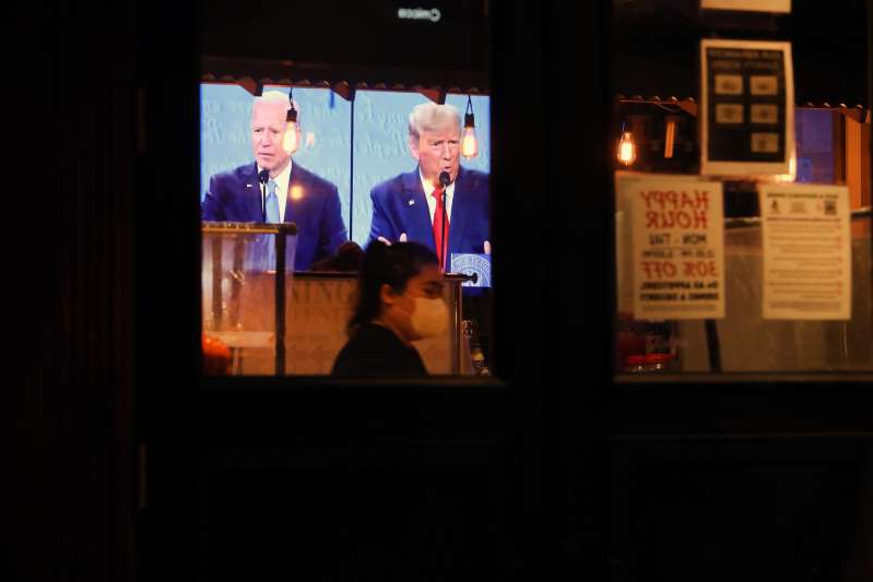 Donald Trump, Joe Biden are posing for a picture: The final debate between President Donald Trump and Joe Biden plays on a restaurant television in Manhattan on October 22, 2020 in New York City.
