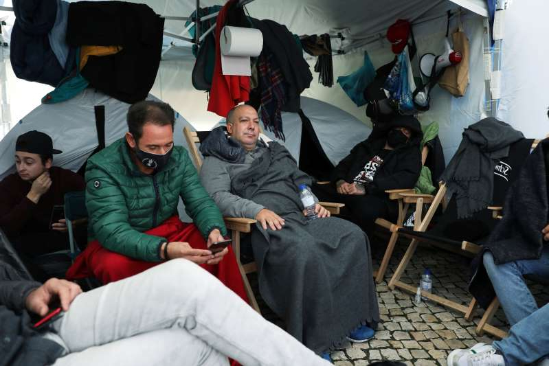 a group of people sitting on a bed: Restaurant owners on hunger strike outside Portuguese parliament