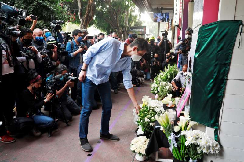 a group of people walking down the street: A member of the French community living in Mexico places flowers at an altar outside a restaurant owned by French businessman Baptiste Jacques Daniel Lormand after he was found murdered, in Mexico City