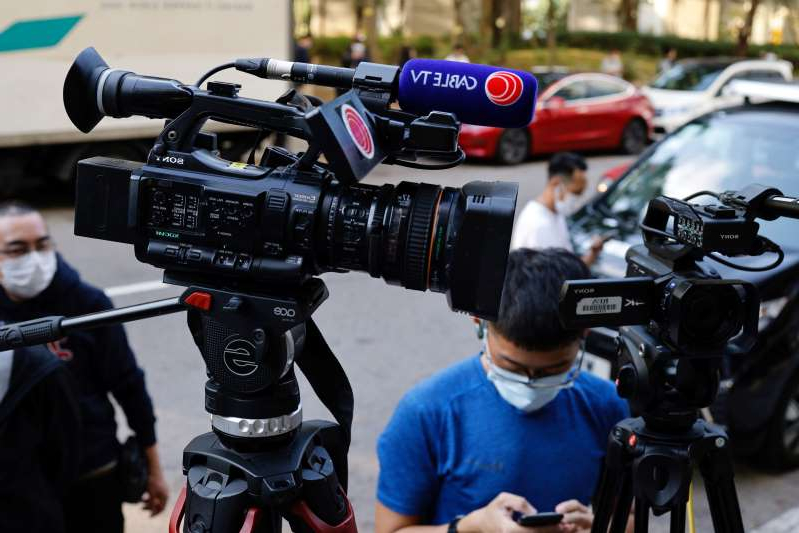 a group of police officers riding on the back of a motorcycle: The logo of Cable TV news is seen on a camera outside its building after about 100 members of staff have been laid off in Hong Kong