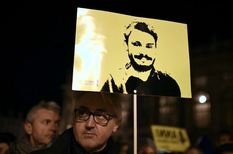 a man holding a sign: Activists of human rights organization Amnesty International take part in a demonstration in Turin Italy on January 25, 2020 to mark the fourth anniversary since the disappearance of Italian student Giulio Regeni who was found dead in Egypt
